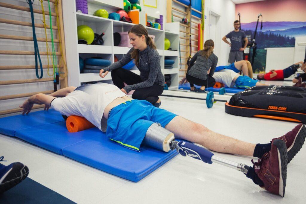 osoba niepełnosprawna z protezą nogi ćwiczy z rehabilitantem